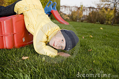 Positive child lay with slide on green grass