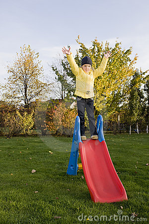 Positive child stay on slide with  green grass ar