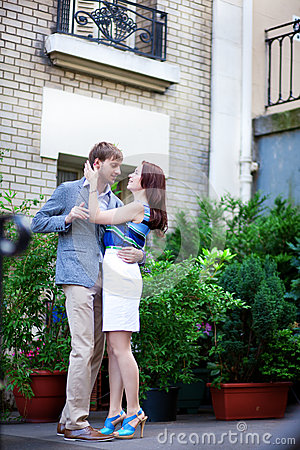Positive couple hugging near their house on Montmartre in