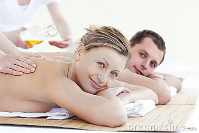 Positive couple receiving a back massage with oil