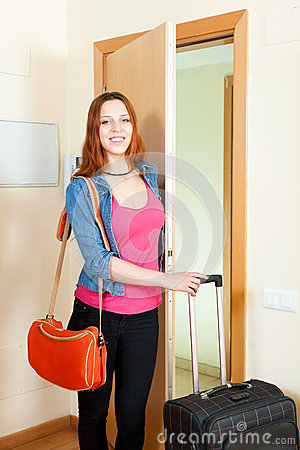 Positive cute red-haired girl with luggage in home going on holi