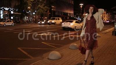 Positive fashionable woman walking on night street stock video