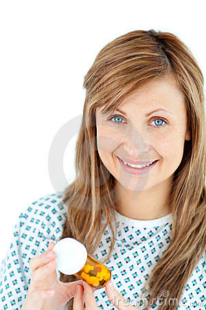 Positive female patient holding pills and smiling