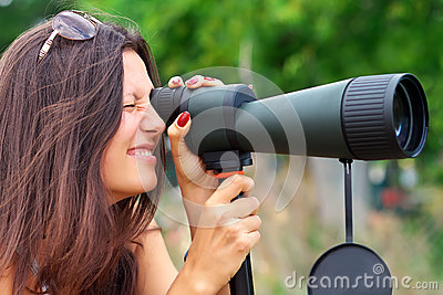 Positive girl watching in spotting scope.