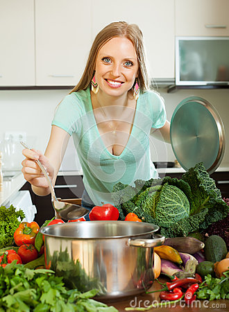 Positive housewife cooking fresh vegetables