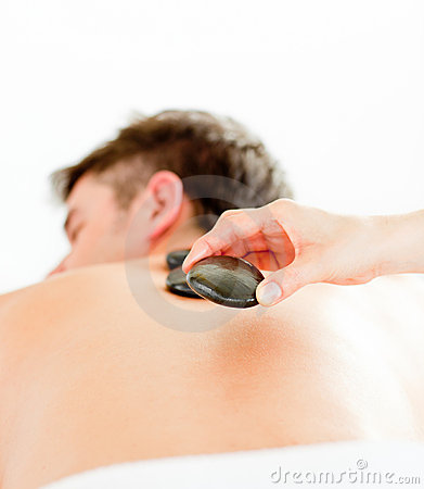 Positive man having a back massage with hot stones