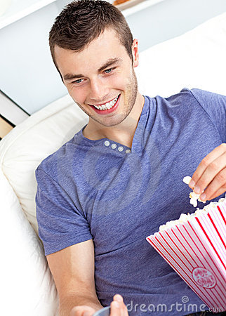 Positive man holding a remote and eating popcorn