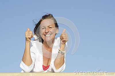 Positive mature woman thumbs up outdoor