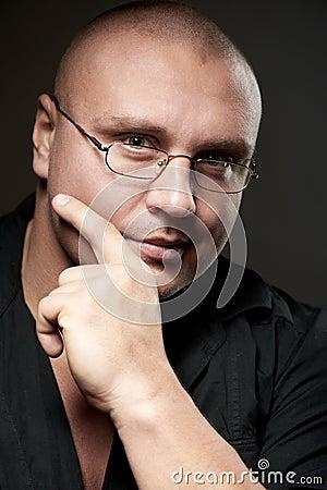Positive portrait of serious man in eyeglasses