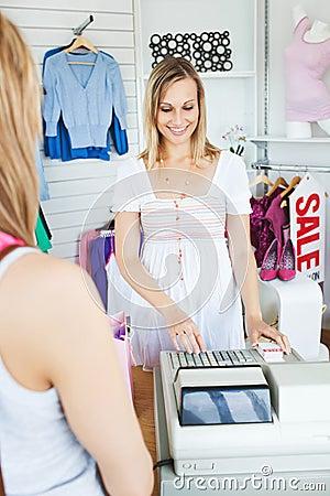 Positive saleswoman using the cash register