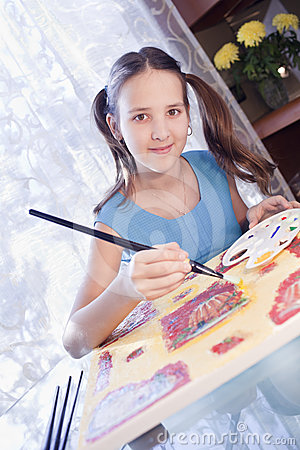Positive school girl are painting at home