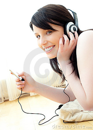 Positive teenager listening to music on the floor
