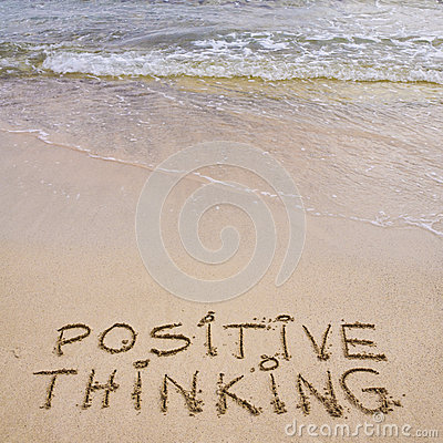 Positive Thinking message written on sand, with waves in background