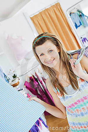 Positive woman choosing clothes and smiling