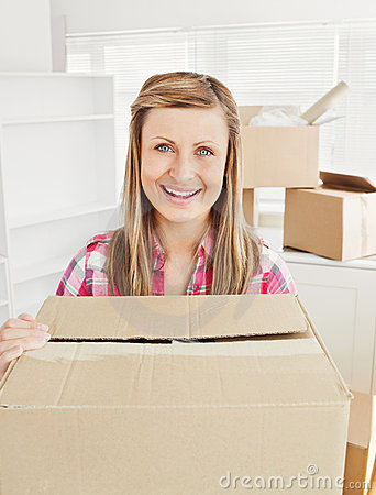 Positive woman holding a box in her new house