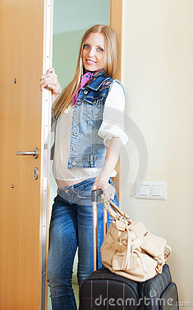 Positive woman in jeans with luggage
