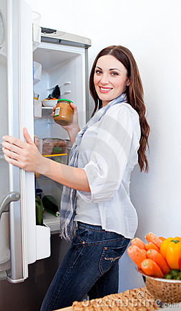Positive woman taking something of the fridge