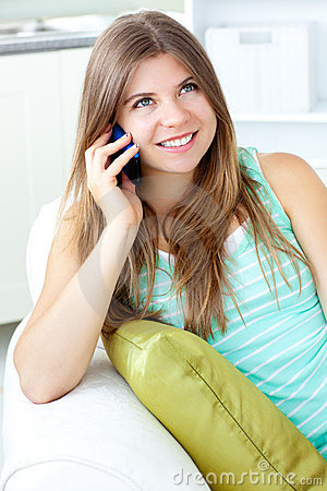 Positive woman talking on phone sitting on a sofa
