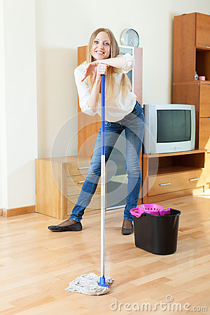 Positive  woman washing parquet floor with mop