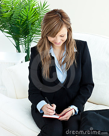 Positive young businesswoman taking notes at home