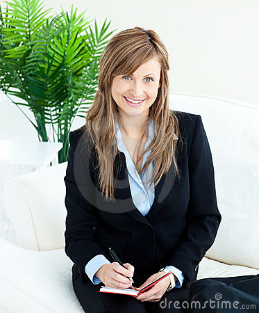 Positive young businesswoman taking notes smiling