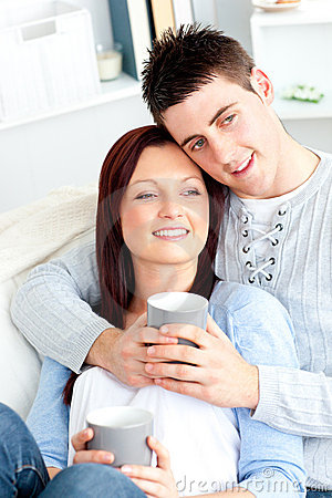 Positive young couple drinking coffee on a sofa