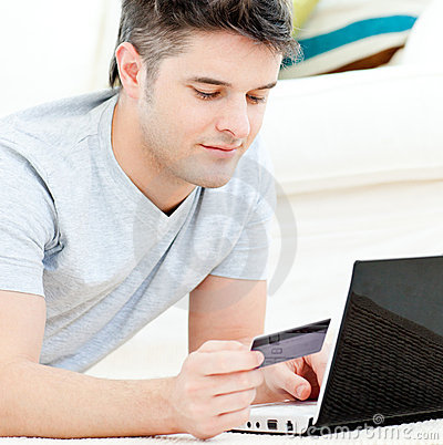 Positive young man holding a card using his laptop