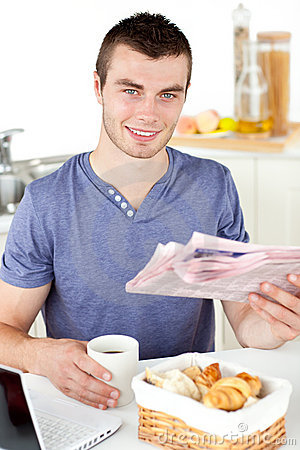 Positive young man holding a cup and a newspaper