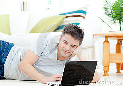 Positive young man using his laptop on the floor