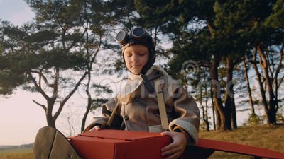 Positiver kleiner Versuchsjunge unter Bäumen im Spaßpappflachen Kostüm, das Retro- Fliegersuperheld-Glaszeitlupe trägt stock video footage