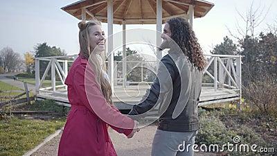 Positives biraziöses junges Ehepaar, das vor dem Pavillon im Herbstpark steht, lacht und redet Happy hippie man und stock footage