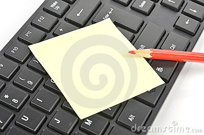 Post-it note, keyboard and pencil