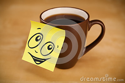 Post-it note with smiley face sticked on cup Stock Photo