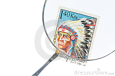 Postage stamp under magnifier with tweezers