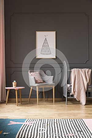 Free Poster Above Grey Armchair With Pillow In Baby`s Bedroom Interio Stock Images - 126408974