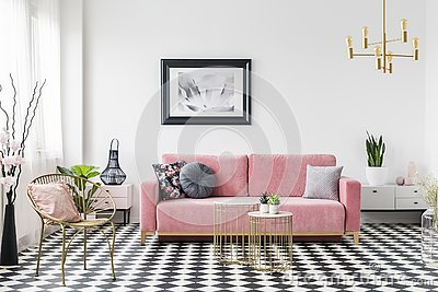 Poster above pink sofa in living room interior with gold armchair on checkered floor. Real photo Stock Photo