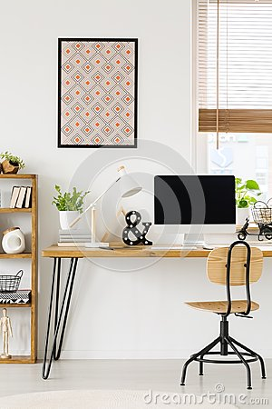 Free Poster On White Wall Above Wooden Desk With Lamp And Desktop Com Stock Photo - 122820230