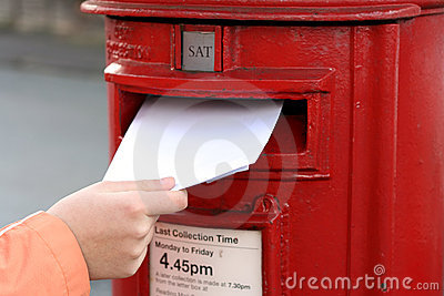 Posting letter to red british postbox