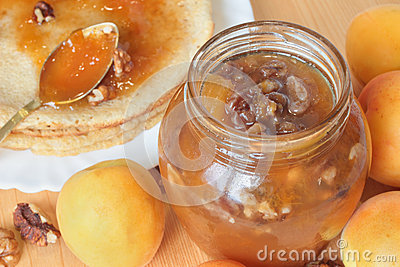 A pot of apricot jam with walnuts