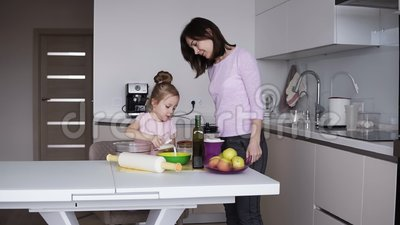 Potomstwa matka i córka w domów ubraniach robią ciastu dla blinów w istnej jaskrawej kuchni Nalewać mleko w puchar zdjęcie wideo