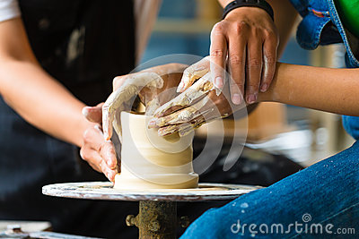 Potter creating clay bowl on turning wheel