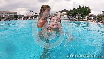 Pouco menina feliz sem dentes de leite e sua natação da mamã na associação video estoque