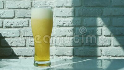 Pour beer into a glass. White background stock footage