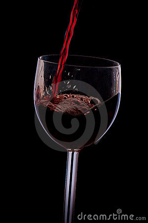 Pour the wine into the glass on a black background