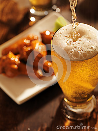 Free Pouring Beer With Chicken Wings In Background. Stock Photo - 30669050