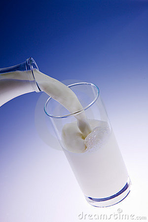 Pouring creamy fresh milk in a transparent glass