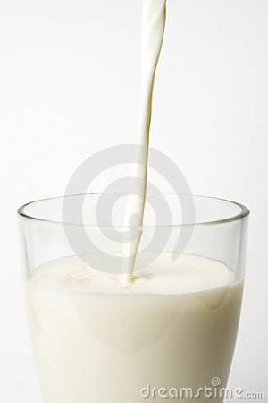 Pouring fresh glass of milk isolated