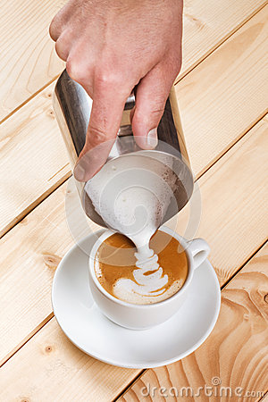 Pouring frothed milk into a cup of coffee, pattern creation