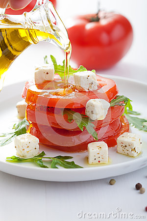 Pouring olive oil over salad with beef tomatoes and feta