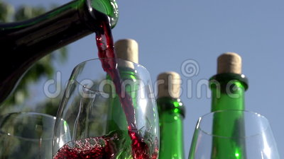 Pouring Red Wine in Goblet. Red wine pouring down from a bottle into a glass on a background of wine bottles. Slow Motion at a rate of 240 fps stock video footage
